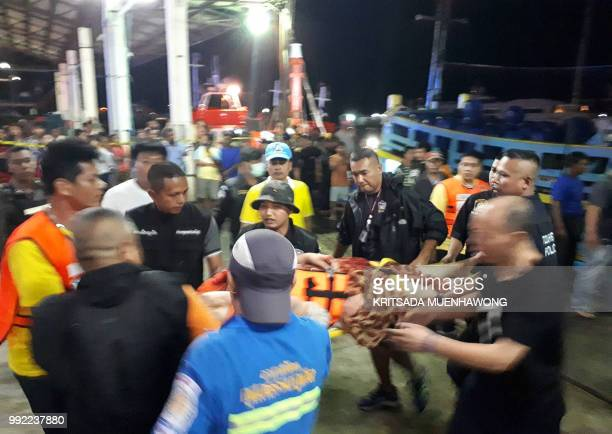 TOPSHOT Thai rescue and paramedic personnel attend to rescued passengers of capsized tourist boat in rough seas at a port in Phuket on July 5 2018...