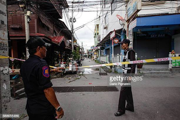 Thai rescue volunteer and a police officer stand at the site of an explosion on Friday August 12 2016 in Hua Hin Thailand A series of coordinated...