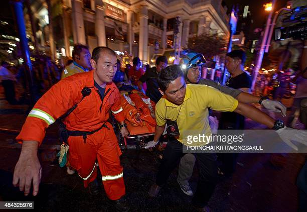 Thai rescue workers carry an injured person after a bomb exploded outside a religious shrine in central Bangkok late on August 17 2015 killing at...