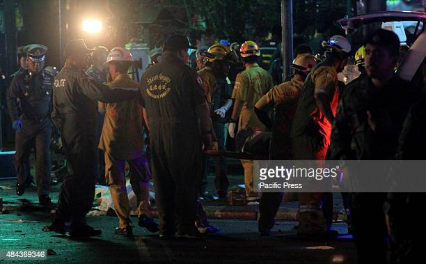 Thai rescue workers carry an injured person after an explosion at the Erawan shrine in downtown Bangkok at the Ratchaprasong intersection of...