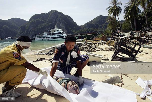 Thai rescue workers cover the body of a baby on the beach December 28 2004 on Phi Phi Village on Ton Sai Bay Thailand On Phi Phi Island hundreds were...