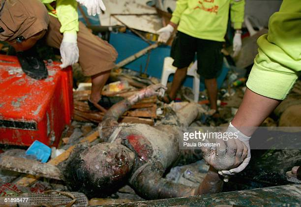 A Thai rescue workers pull a body out of a shop where 7 people were found on December 28 2004 in Phi Phi Village Thailand On Phi Phi island hundreds...