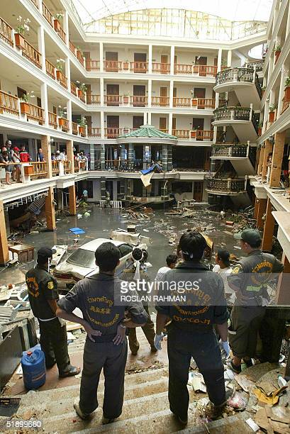 Thai rescue workers wait for their colleagues searching for dead bodies in the basement of the Sea Pearl Beach hotel resort along Patong beach in...