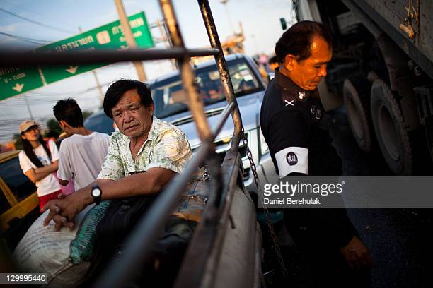 Thai resident displaced by flooding sits in the back of a pickup as a Thai Police officer looks on after taking a break from relief support on...