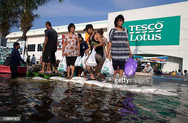 Thai residents make their way through the flooded streets after shopping at Tesco Lotus store October 21 2011 in Pathumthani on the outskirts of...