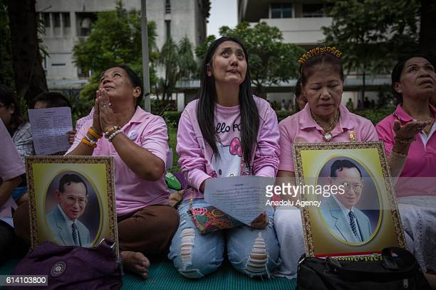 Thai Royalists cries while holding a portraits of Thailand's King Bhumibol Adulyadej as his health has deteriorated and he's now in an unstable...