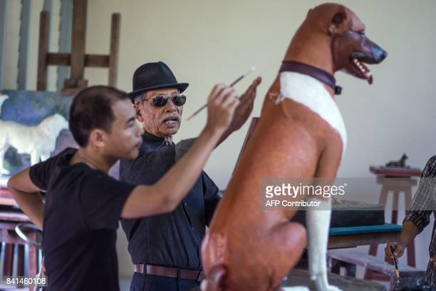 Thai sculptor Chin Prasong gives indications to Pitchapong Parsing as Parsing gives the finishing touches of paint to a sculpture of one of the dogs...