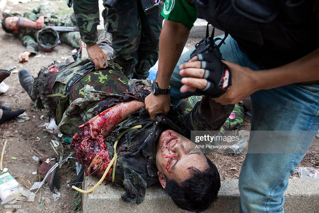Thai security forces attempt to help a Thai soldier hit by a grenade on May 19, 2010 in Bangkok, Thailand. At least 5 people are reported to have died as government forces attempted to overrun barricades raised in and around the city centre by anti-government protestors. Red-shirt leaders have now surrendered, ending their blockade following a sixth day of violence, leaving the army in control and a night time curfew to be imposed.