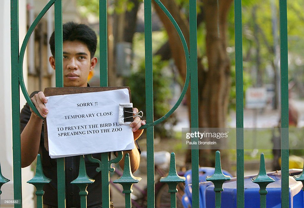 A Thai security guard holds a sign showing that the Dusit Zoo is closed for fear of spreading the deadly bird flu February 3, 2004 in Bangkok, Thailand. An outbreak of bird flu has ravaged poultry farms and could devastate the country's chicken export sector, worth 1.5 billion dollars, which is the fourth largest in the world.