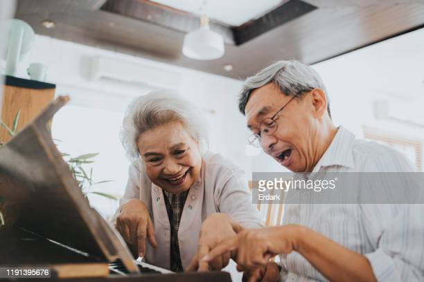 thai senior couple enjoy playing paino at home - keyboard player stock pictures, royalty-free photos & images