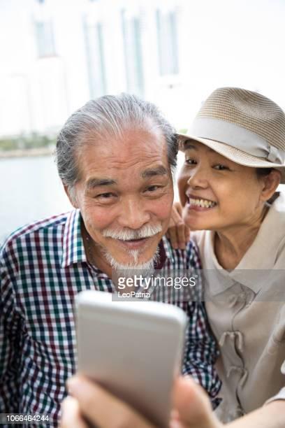 Thai senior couple take a selfie on vacation