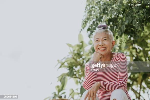 retrato hipster sênior tailandês ao lado do jardim - alegria - fotografias e filmes do acervo