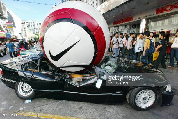 Thai shoppers look on at an advertisement for Nike at Euro 2004 showing a BMW sports sedan buckling under the weight of giant football outside a...