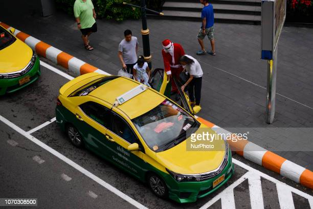A Thai shopping mall worker dressed up as Santa Claus helps a shopper load shopping goods to a taxi at a shopping mall in Bangkok Thailand 08...