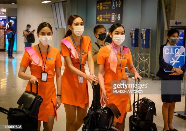 Thai Smile cabin crew members wearing protective facemasks walk next to an airport official waiting for CIQ passengers at Suvarnabhumi International...