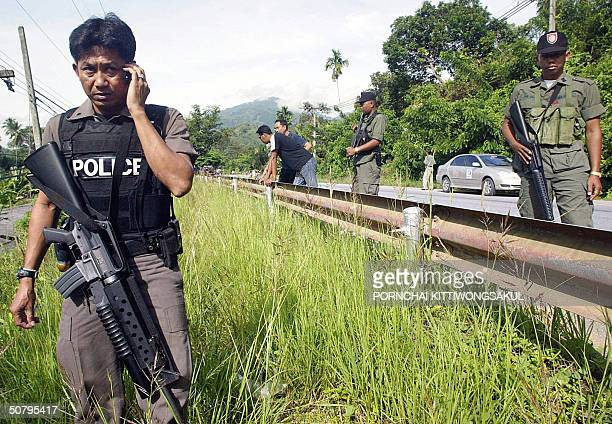 Thai soldier communicates on his mobile phone during a search operation by security officials after overnight violence in the Tanto district of Yala...