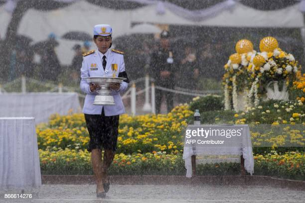 A Thai soldier in dress uniforms carries flowers as a sign of respect for the late Thai king Bhumibol Adulyadej at the King Rama V Monument in...