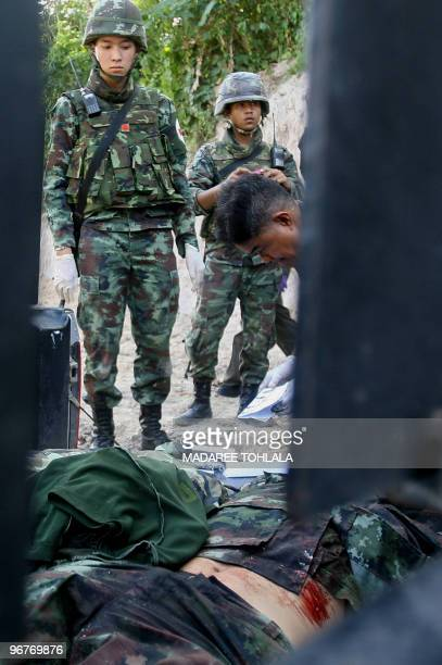 A Thai soldier looks at the bodies of two Thai soldiers killed in clashes with suspected separatist Muslim militants in the Rueso district in...
