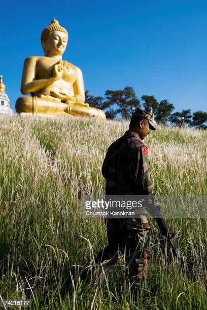 Thai soldier patrols next to The Gient Buddha Statue at Khao Kong Temple May 22 Narathiwat province Thailand More than 2100 people have been killed...