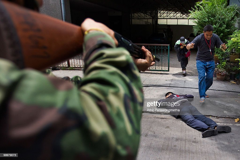A Thai soldier points his rifle at Red-shirt protesters as they surrender within their encampment on May 19, 2010 in Bangkok, Thailand. At least 5 people are reported to have died as government forces sought to overrun barricades raised in and around the city centre by anti-government protestors. Red-shirt leaders have now surrendered, ending their blockade in the aftermath of a sixth day of violence, leaving the army in control and a night time curfew to be imposed.
