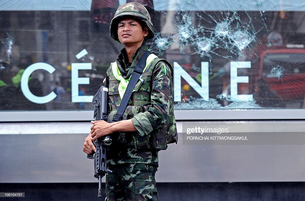 A Thai soldier stands guard as others clear debris at the anti-government main protest area in Bangkok on May 21, 2010. Thailand picked up the pieces after violence and mayhem triggered by a crackdown on anti-government protests, as the focus swung to recovery and reconciliation in a divided nation.