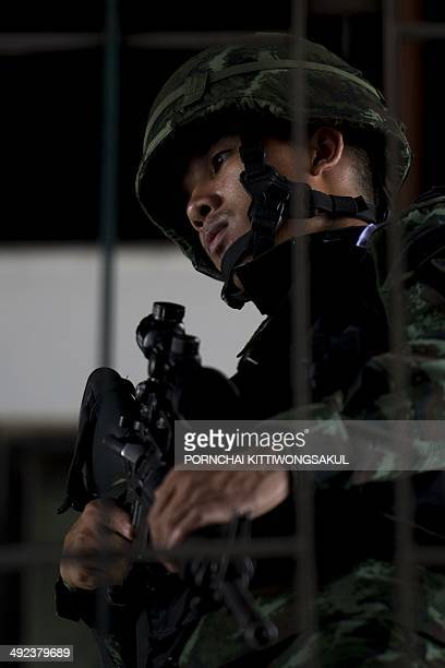 A Thai soldier stands guard during a visit by Army chief General Prayut ChanOCha at the Army Club in Bangkok on May 20 2014 Thailand's army declared...