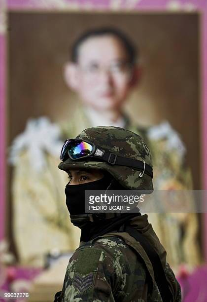 A Thai soldier stands guard in front of a portrait of Thai King Bhumibol Adulyadej around near the Red Shirt antigovernment protest site in downtown...