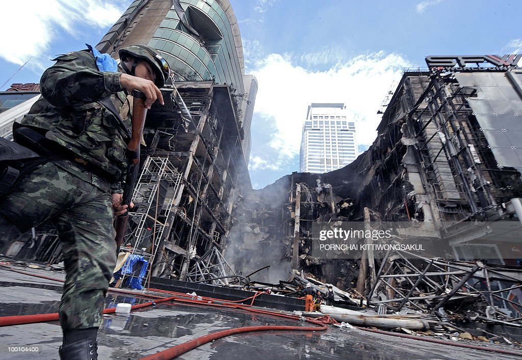 Thai soldier walks past Thailand's biggest shopping mall - Central World - after it was set ablaze from anti-government protesters in Bangkok on May 21, 2010. Thailand picked up the pieces after violence and mayhem triggered by a crackdown on anti-government protests, as the focus swung to recovery and reconciliation in a divided nation.