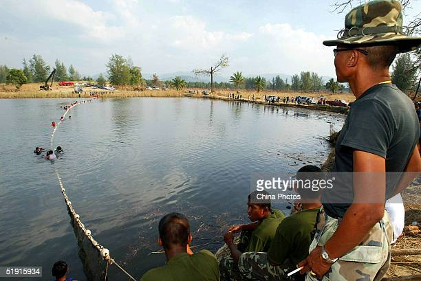 Thai soldiers attempt to catch an Indo-Pacific humpback dolphin to the ocean for release after they rescued it from a lake left behind by last week's...