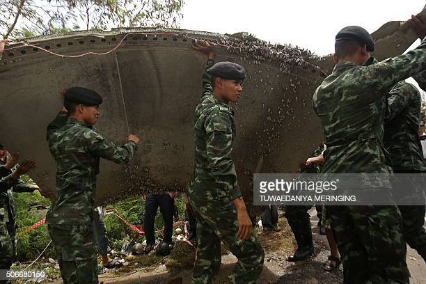 Thai soldiers carry a piece of suspected aircraft debris after it was found by fishermen on January 23, at a beach in the southern province of Nakhon...