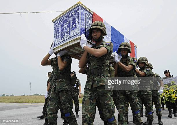 Thai soldiers carry the coffin of a slain colleague to a cargo plane at Narathiwat airport in Thailand's restive southern Narathiwat province on...