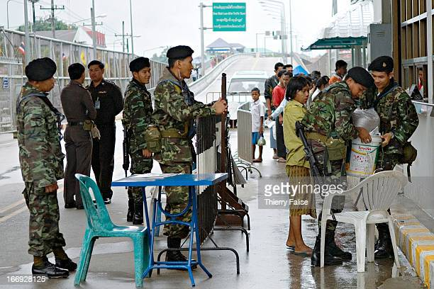 Thai soldiers check and search Burmese migrants who are crossing the ThaiBurma border at the socalled 'Friendship bridge' between Myawadi in Burma...