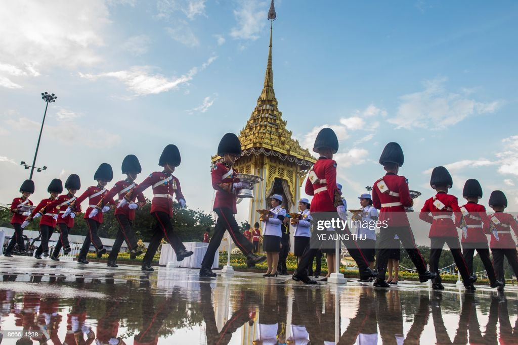 Thai soldiers in dress uniforms carry flowers as a sign of respect for the late Thai king Bhumibol Adulyadej at the King Rama V Monument in Bangkok on October 26, 2017. A sea of black-clad mourners massed across Bangkok's historic heart early on October 26 as funeral rituals began for King Bhumibol Adulyadej, a revered monarch whose passing after a seven-decade reign has left Thailand bereft of its only unifying figure. /