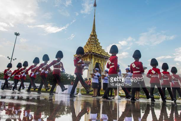 Thai soldiers in dress uniforms carry flowers as a sign of respect for the late Thai king Bhumibol Adulyadej at the King Rama V Monument in Bangkok...