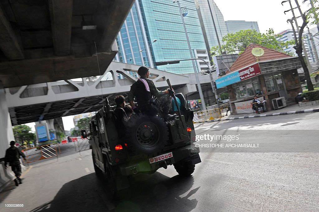 Thai soldiers patrol the deserted streets of Bangkok a day after an assault on an anti-government protest site in downtown Bangkok on May 20, 2010. Thai authorities imposed a curfew for three more nights in Bangkok and 23 other provinces to quell conflict in the aftermath of an army offensive against anti-government protesters. AFP PHOTO/Christophe ARCHAMBAULT