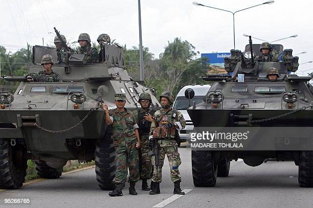 Thai soldiers stand beside armored vehicles at the site of a bomb attack on a bus which was transporting Thai soldiers in Thailand's restive southern...