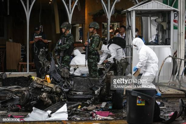 Thai soldiers stand guard as a forensics unit inspects the aftermath of a car bomb which left at least 50 wounded in front of Big C supermarket in...