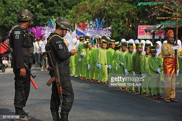 Thai soldiers watch as Muslim schoolchildren participate in the opening parade of the Kadrika Sampan festival in Rangae district in Thailand's...