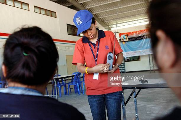 Thai staff member from IOM's Migrant Health Project explains how to use a radio distributed to Burmese migrants at the Learning center at Baan Nham...