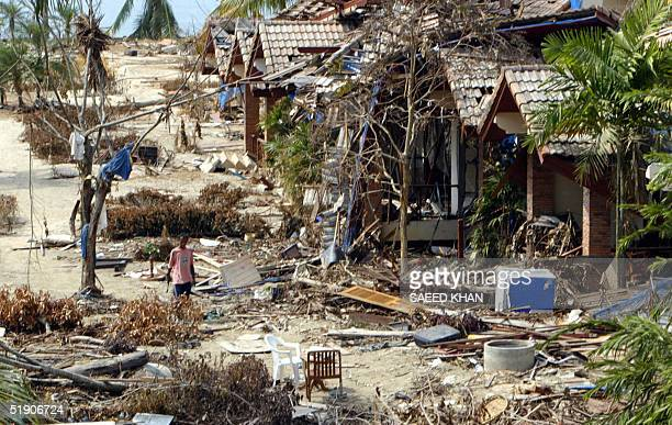 Thai staff of Khao Lak natural resort walks throught the debris of washed away banglows at the shoreline of Khao Lak beach 01 January 2005 Aid...