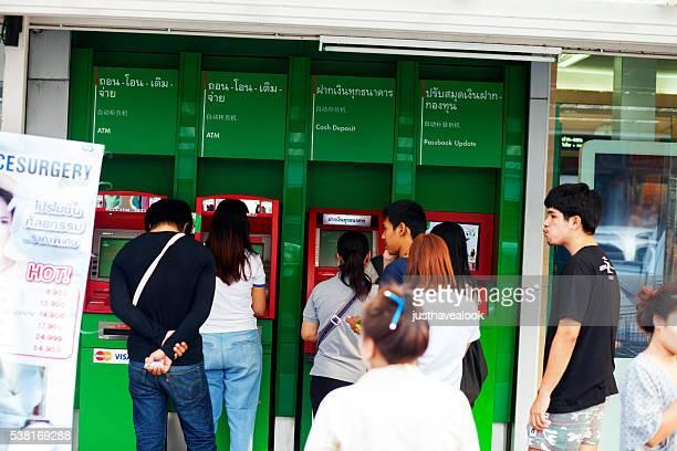Thai standing in queue at ATM