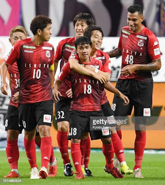 Thai striker Chanathip Songkrasin of Consadole Sapporo is congratulated by his teammates after scoring an equalizer during the first half of a 11...