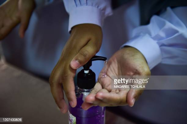 A Thai student applies hand sanitiser as a preventive measure against the COVID19 coronavirus before attending a ceremony at Attarkiah Islamic School...