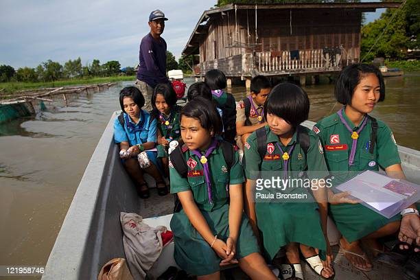 Thai students get a boat home rather than the usual school bus as roads are submerged along the swollen Yom river August 24 2011 Phinchit Thailand...