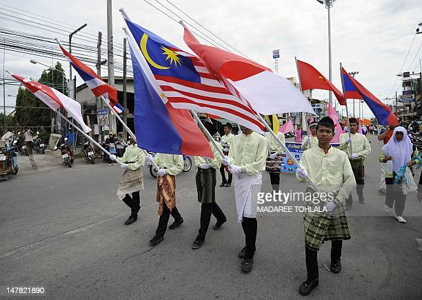 Thai students holding asean national flags walk amongst a parade taking place during a local sport games tournament in Narathiwat province on July 4...