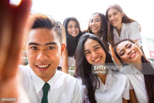 Thai students in uniform in Bangkok take a break together