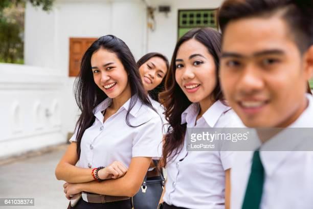 Étudiants thaïlandais en uniforme posant en regardant la caméra hors de l'Université