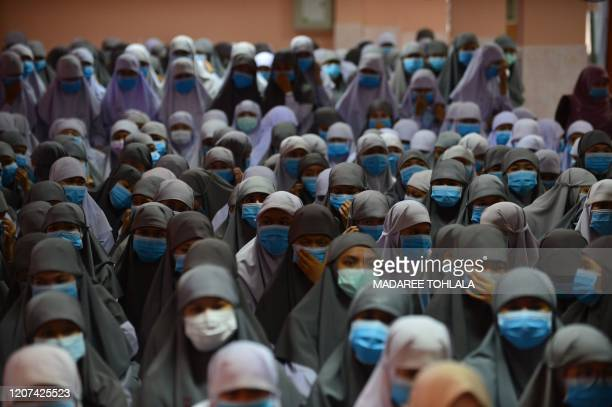 TOPSHOT Thai students wear face masks donated by a school official as a preventive measure against the COVID19 coronavirus during a ceremony at...