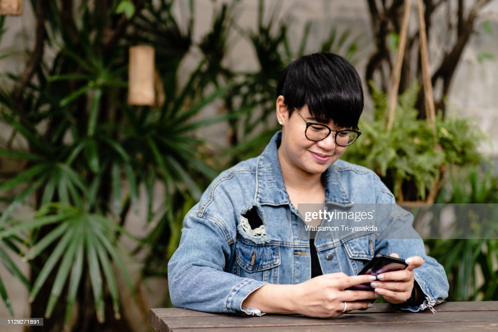 Thai stylish middle-aged woman with phone : Stock Photo