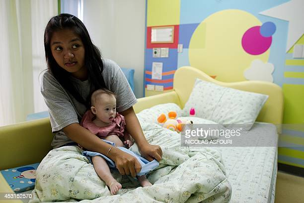 Thai surrogate mother Pattaramon Chanbua holds her baby Gammy born with Down Syndrome at the Samitivej hospital Sriracha district in Chonburi...